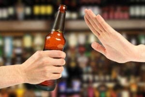 A Hand Of Someone Overcoming Alcoholism Rejecting A Bottle Of Beer